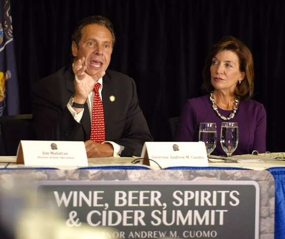Gov. Andrew Cuomo sits at a podium at the Wine, Beer, Spirits and Cider Summit in Albany. (Skip Dickstein / Times Union)