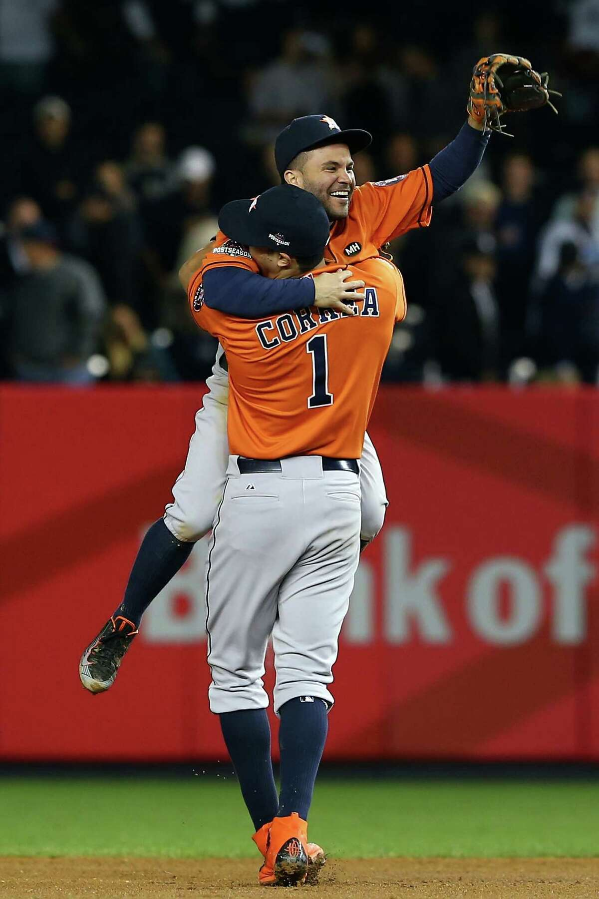 NEW YORK, NY - OCTOBER 06: Jose Altuve #27 and Carlos Correa #1 of the Houston Astros celebrate defeating the New York Yankees in the American League Wild Card Game at Yankee Stadium on October 6, 2015 in New York City. The Astros defeated the Yankees with a score of 3 to 0. (Photo by Elsa/Getty Images)