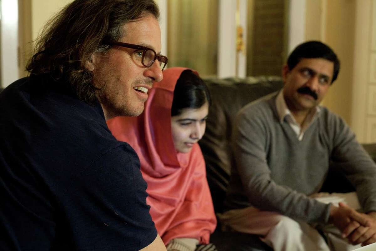 Director Davis Guggenheim, left, visits with Malala Yousafzai and Ziauddin Yousafzai in Birmingham, England, during the filming of the documentary