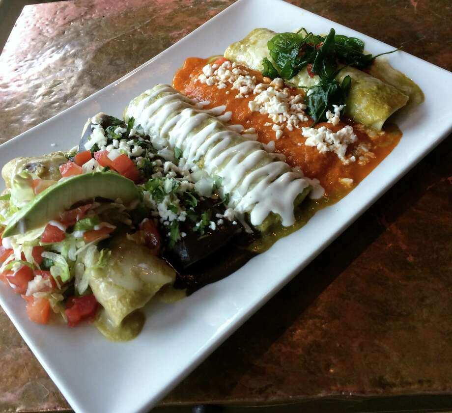 Featured is a five enchilada plate (left to right La Fonda Suizas, enfrijoladas, verde de pollo, rojas de queso, and espinaca) Photo: Chris Waters Dunn
