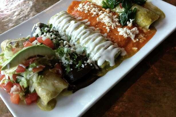 Featured is a five enchilada plate (left to right La Fonda Suizas, enfrijoladas, verde de pollo, rojas de queso, and espinaca)