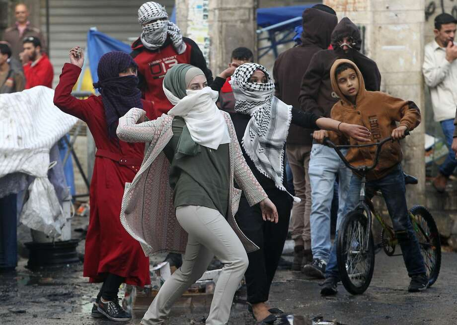 Palestinian young women throw stones toward Israeli security forces during clashes in the West Bank town of Hebron. Photo: Hazem Bader, AFP / Getty Images