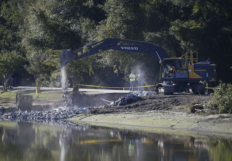 Work crews use an excavator to stabilize a dam in Columbia, S.C. Heavy rain has caused flooding in parts of the state. Photo: John Bazemore, Associated Press