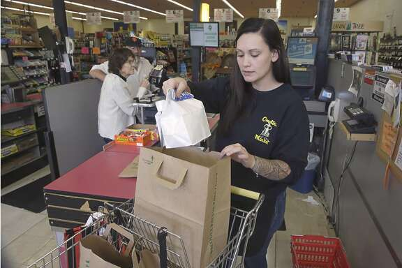 Checker Brittney Bounds bags groceries for customer Esther Franklin, left, at Compton's Market Tuesday, Oct 6, 2015 in Sacramento, Calif.  Calif., Gov. Jerry Brown signed an equal pay measure, SB358, by state Sen. Hannah-Beth Jackson, D-Santa Barbara, Tuesday, that lets female employees challenge pay discrimination based on the wages a company pays to other employees who do similar work.(AP Photo/Rich Pedroncelli)