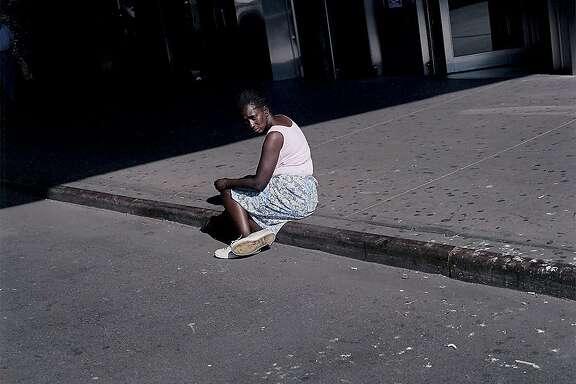 Woman sitting on sidewalk, New York - from the series American Night, 2002.