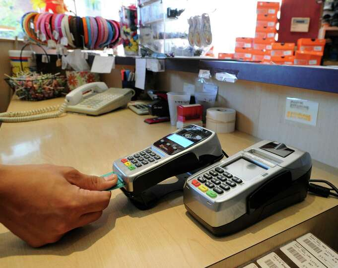 Little Eric of Greenwich shoe store employee Javier Priego demonstrates the new credit card reader i