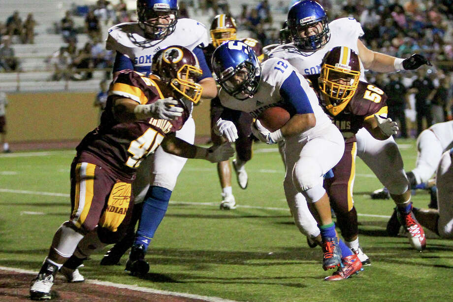 Somerset's Roger Villegas (center) scores a fourth quarter touchdown despite the efforts of Harlandale's Robert Palomino (left) and Christopher Laque (right) during their game at Harlandale Memorial Stadium on Thursday, Sept. 3, 2015. Somerset beat the Indians 21-0. Photo: Marvin Pfeiffer /San Antonio Express-News / Express-News 2015