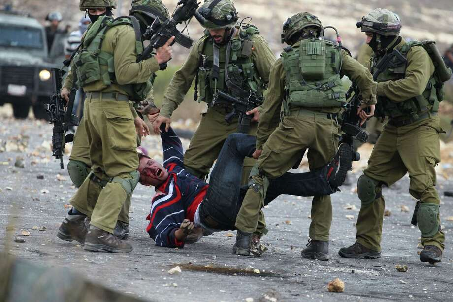 Israeli soldiers detain a wounded Palestinian stone thrower after infiltrated members of the Israeli security forces shot at protesters Wednesday during clashes in Beit El, Israel.  Photo: ABBAS MOMANI, Stringer / AFP