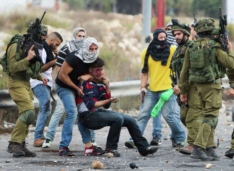 Israeli soldiers and undercover police officers detain a wounded Palestinian demonstrator during clashes near Ramallah, in the West Bank. Photo: Majdi Mohammed /Associated Press / AP