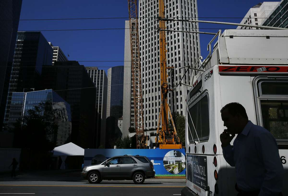 A pedestrian walks past the Temporary Transbay Terminal Oct. 6 2015 in San Francisco, Calif.