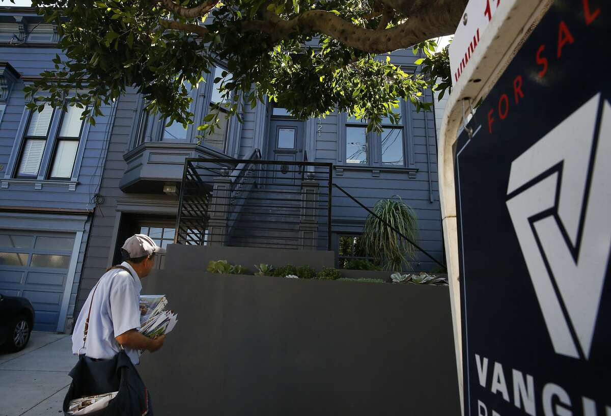 A postman walks past a four bedroom home for sale listed on Zillow.com for $3.19 million in Noe Valley Oct. 6 2015 in San Francisco, Calif.