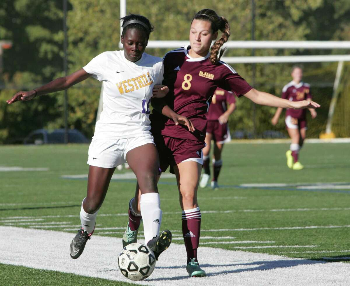 Westhill's Chelsea Domond and St. Joseph's Tory Bike battle for the ball during the first half of a girls varsity soccer game in Stamford, Conn. on Oct. 7, 2015.