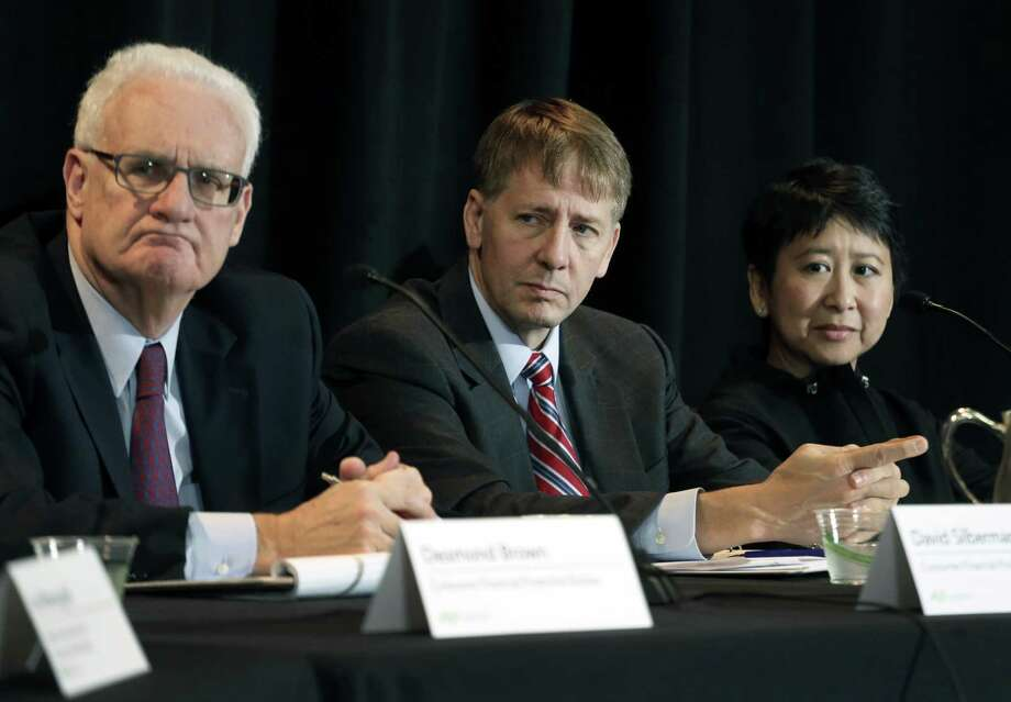Consumer Financial Protection Bureau Director Richard Cordray, center, and, left and right, his CFPB colleagues David Silberman and To-Quyen Truong listen to a speaker, during a a hearing in Denver where his agency's proposal on arbitration was discussed, in Denver, Colo., Wednesday, Oct. 7, 2015. If enacted, the plan would severely curtail a contentious practice called mandatory arbitration, which consumer advocates have long argued does a disservice to people who have disputes with banks, credit card issuers and other financial service providers. (AP Photo/Brennan Linsley) Photo: Brennan Linsley, STF / AP