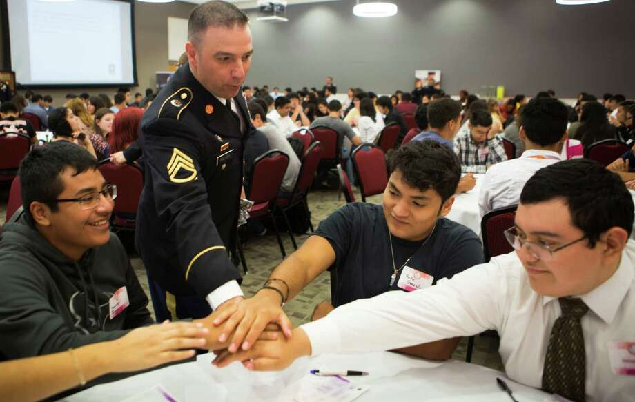 U.S Army Sergeant first class Antonio Hinojosa, center, shares a moment with high school students, Santiago Quintana, left, Hector Gonzalez and Daniel Banda, right, after collaborating in a leadership workshop prepared as part of the LOFT STEM Leadership Symposium program, Wednesday, Oct. 7, 2015, in Houston. ( Marie D. De Jesus / Houston Chronicle ) Photo: Marie D. De Jesus, Staff / © 2015 Houston Chronicle