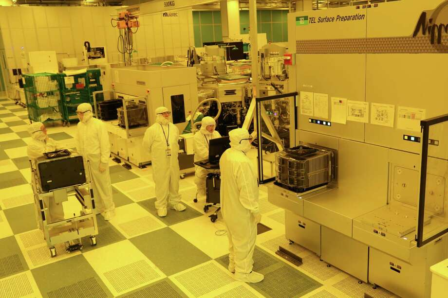 Researchers from Tokyo Electron Ltd. work on a wafer tool at the NanoFabX building at SUNY Polytechnic Institute in Albany on Wednesday, Oct. 7, 2015.
