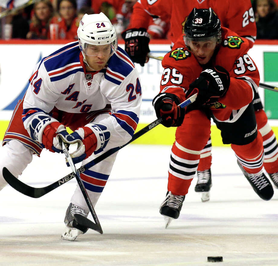 New York Rangers center Oscar Lindberg, left, chases the puck past Chicago Blackhawks right wing Kyle Baun during the first period of an NHL hockey game Wednesday, Oct. 7, 2015, in Chicago. (AP Photo/Nam Y. Huh) ORG XMIT: CXA124 Photo: Nam Y. Huh / AP