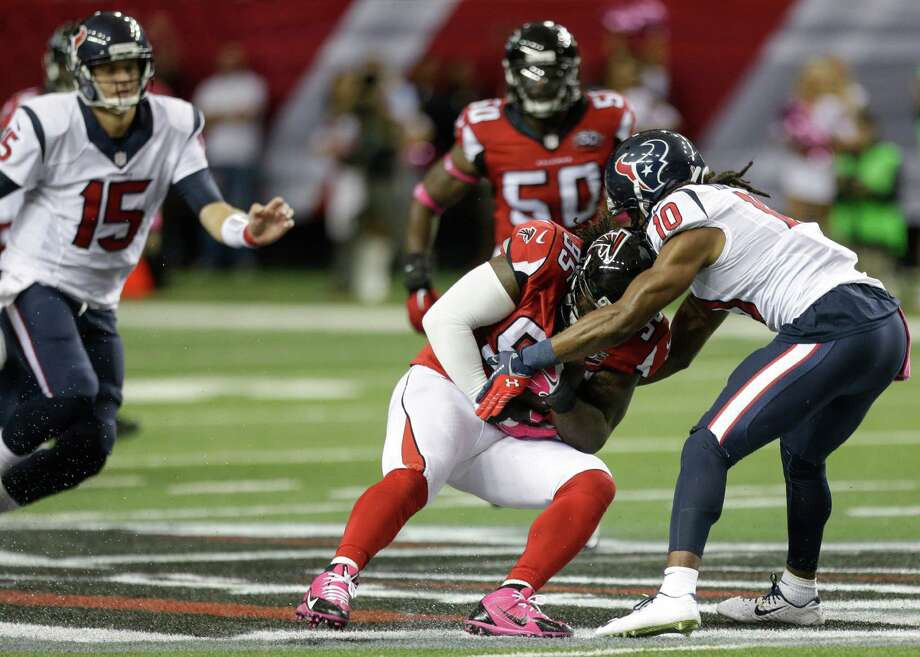 Falcons defensive tackle Jonathan Babineaux snags a pass intended for DeAndre Hopkins, right, for one of the Texans' four turnovers Sunday. Photo: Brett Coomer, Staff / © 2015  Houston Chronicle