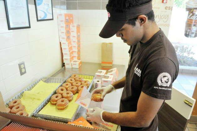 Dunkin' Donuts employee Jefri Nazri boxes up the new croissant donuts at the Dunkin' Donuts at 749 Hoosick St., on Monday, Nov. 3, 2014, in Troy, N.Y. (Paul Buckowski / Times Union archive) Photo: Paul Buckowski / 00029306A