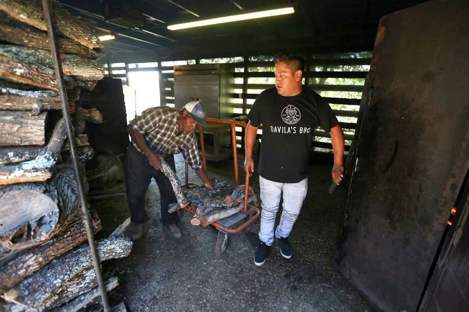 Adrian Davila, right, checks on the smokers at his family's restaurant Davila's BBQ in Seguin. Photo: William Luther /San Antonio Express-News / © 2015 San Antonio Express-News