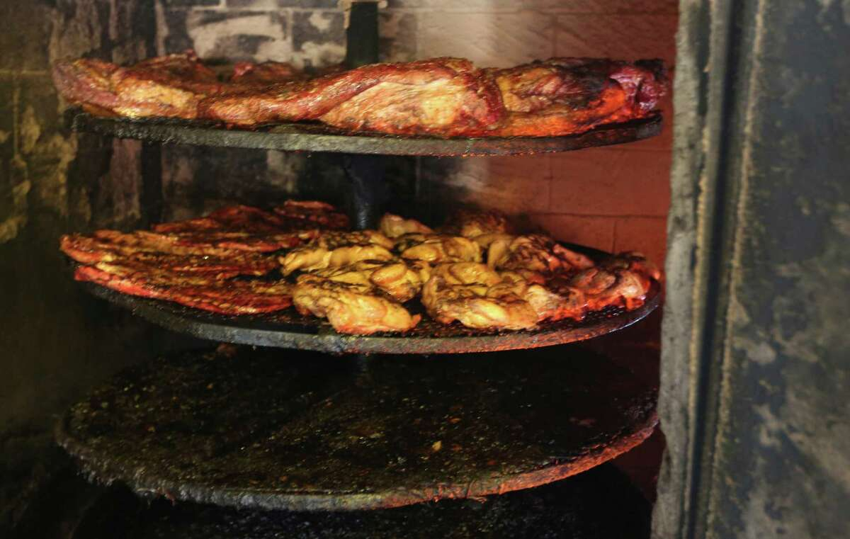 Meat from Seguin's Davila's BBQ is seen as it cooks inside one of the restaurant's several on-site smokers.