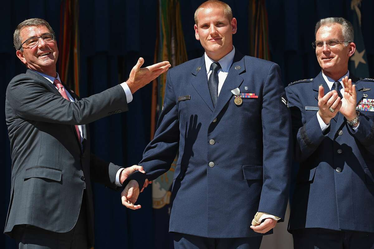 U.S. Air Force Airman 1st Class Spencer Stone (center) is congratulated by U.S. Defense Secretary Ashton Carter (left) and Vice Chairman of the Joint Chiefs of Staff Gen. Paul Selva during an awards ceremony for Stone and two other men who helped stop a gunman on a Paris-bound train last month at the Pentagon September 17, 2015 in Arlington, Virginia. Stone received the Airman's Medal and the Purple Heart medal, Army Specialist Alek Skarlatos received the Soldier's Medal and Anthony Sadler received the Defense Department Medal for Valor. The three men helped overpower gunman Ayoub El-Khazzani, 25, after he opened fire on a Thalys train traveling from Amsterdam to Paris on August 21.