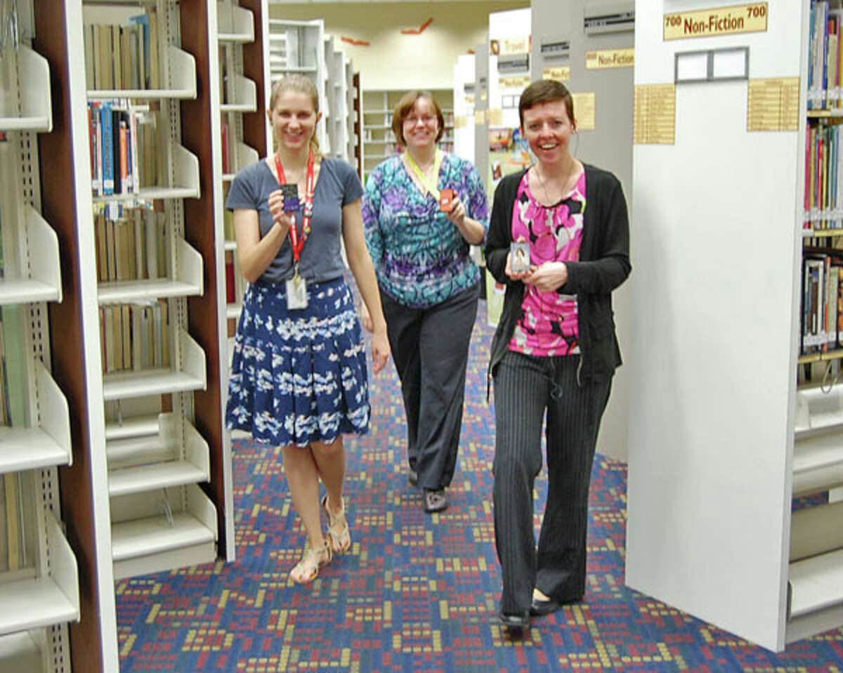 Librarians Gretchen LeCheminant, Cherie Morgan and Chazley Dotson listen to Playaway audiobooks while walking laps inside Sterling Library.