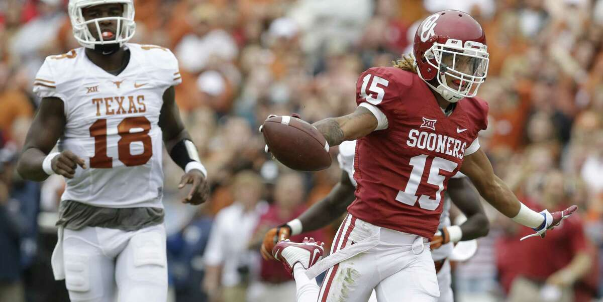 Oklahoma cornerback Zack Sanchez (15) celebrates scoring a touchdown after intercepting a pass against Texas quarterback Tyrone Swoopes (18) during the first half of an NCAA college football game at the Cotton Bowl, Saturday, Oct. 11, 2014, in Dallas. (AP Photo/LM Otero)