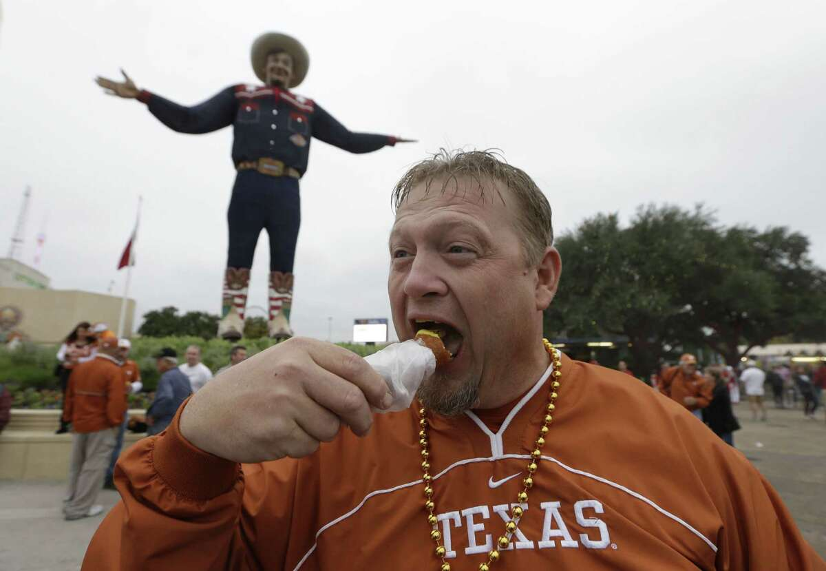 Steve Poole eats a corn dog at the State Fair of Texas outside the Cotton Bowl before the NCAA college football game between Texas and Oklahoma Saturday, Oct. 11, 2014, in Dallas. (AP Photo/LM Otero)