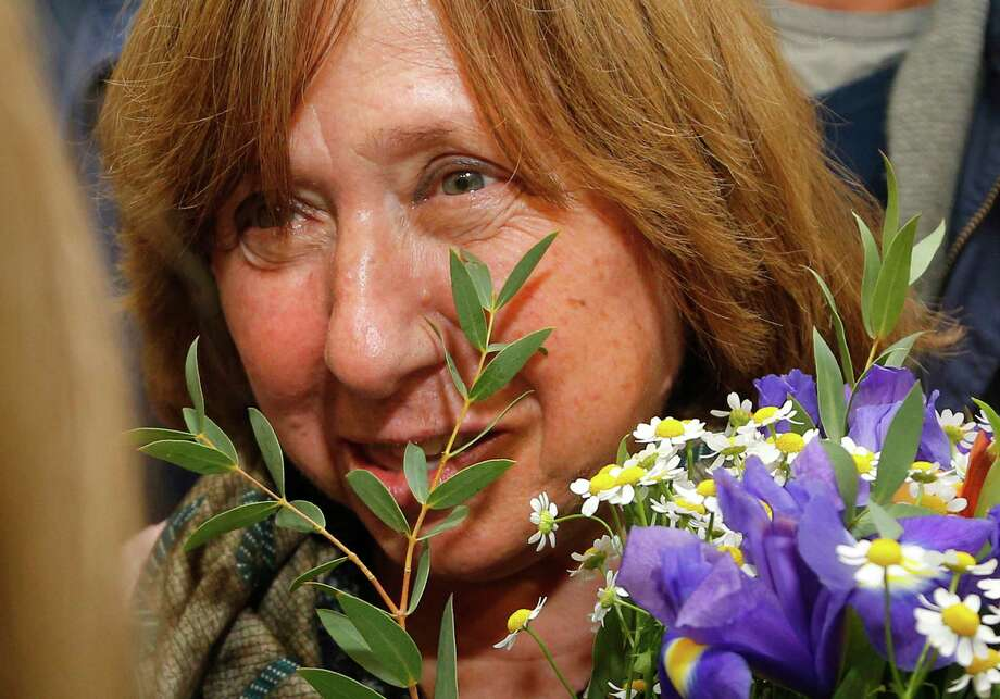 """Belarusian journalist and writer Svetlana Alexievich the 2015 Nobel literature winner, holds flowers as she leaves after a news conference in Minsk, Belarus, Thursday, Oct. 8, 2015. Belarusian writer Svetlana Alexievich won the Nobel Prize in literature Thursday, for works that the prize judges called """"a monument to suffering and courage."""" Photo: Sergei Grits, AP / AP"""