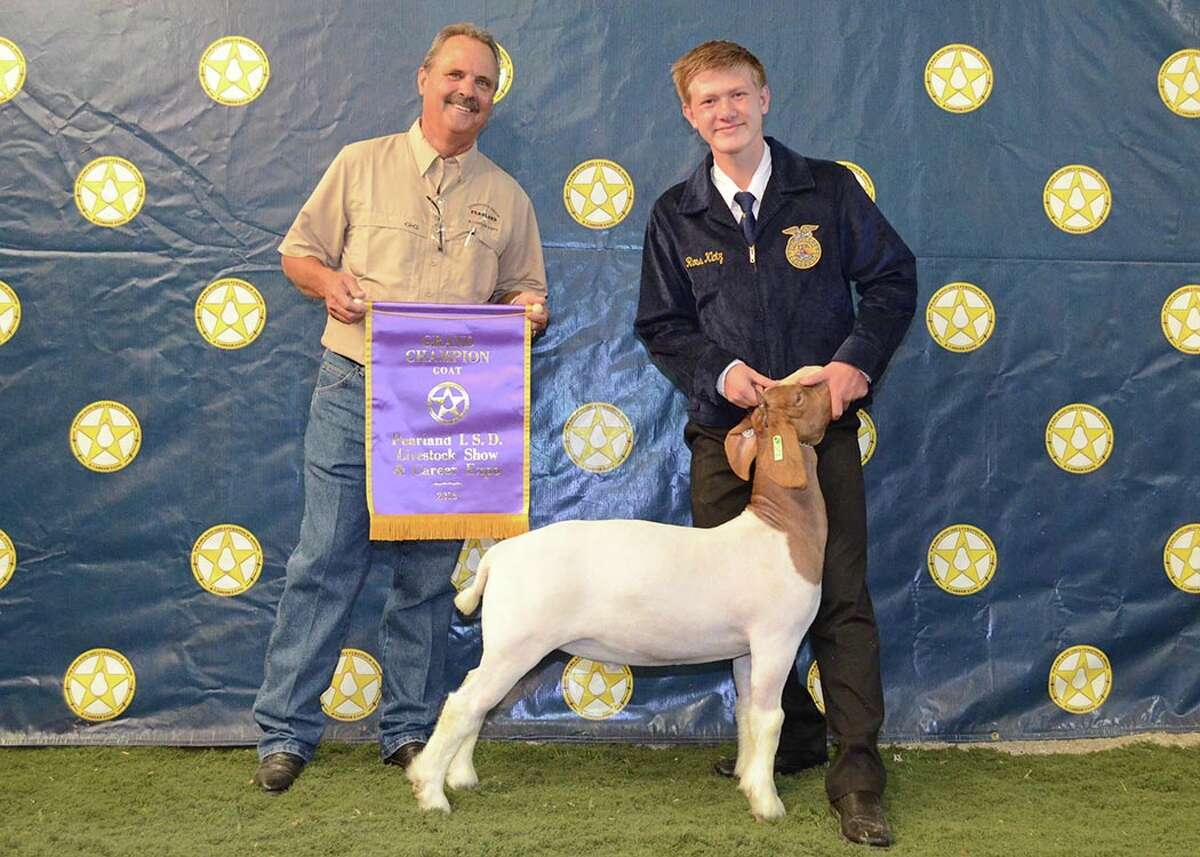 Pearland High School's Daniel Klotz, right, boasts the grand champion goat at the Pearland ISD Livestock Show & Career Expo.