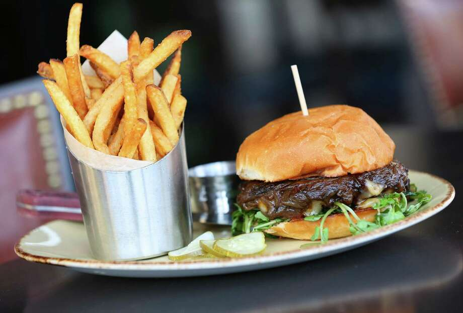 The Aristocrat Burger includes housemade mustard, watercress, ale glazed shallots and muenster cheese on an egg bun. It's served with fries and housemade pickles. Photo: William Luther /San Antonio Express-News / © 2015 San Antonio Express-News
