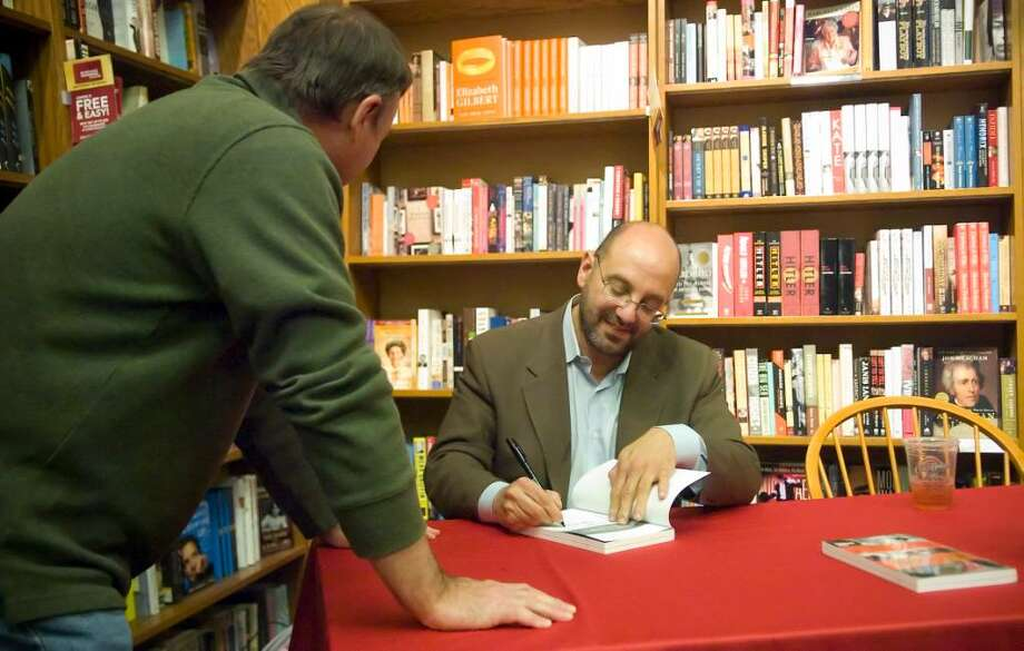 """Writer Irvin Muchnick signs a copy of his new book, """"Chris & Nancy: The True Story of the Benoit Murder-Suicide and Pro Wrestling's Cocktail of Death"""" for Dan McCabe during a book signing at Borders Bookstore in Stamford, Conn. on Thursday, March 25, 2010. Photo: Chris Preovolos / Stamford Advocate"""