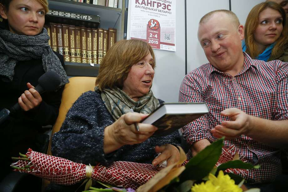 Svetlana Alexievich signs books in Minsk, Belarus, at a news conference after winning the prize. Photo: Sergei Grits, Associated Press