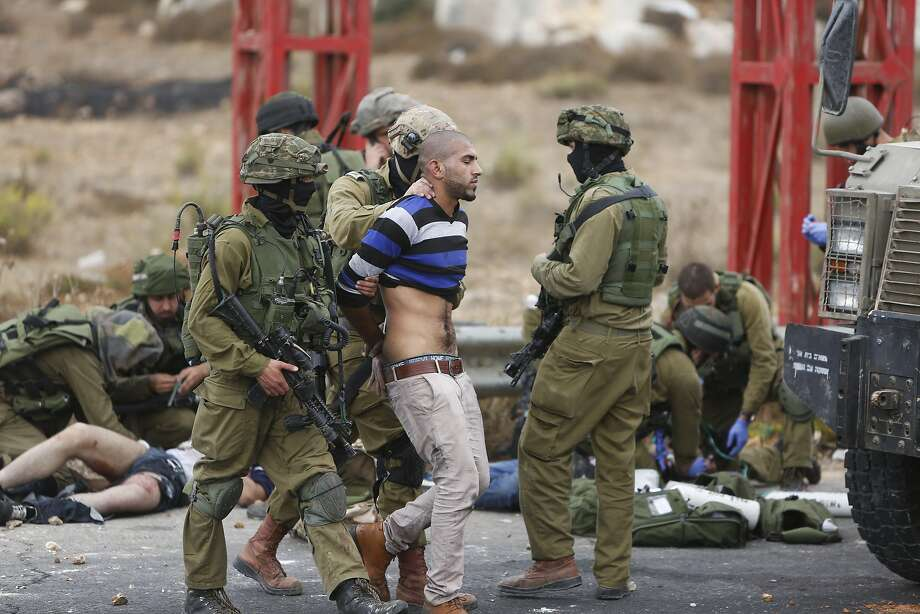 Israeli soldiers arrest a man, while others treat wounded Palestinians near Ramallah, West Bank. Photo: Majdi Mohammed, Associated Press