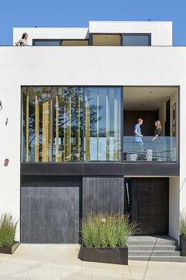 The contemporary facade is defined by precise lines and expansive pieces of glass.