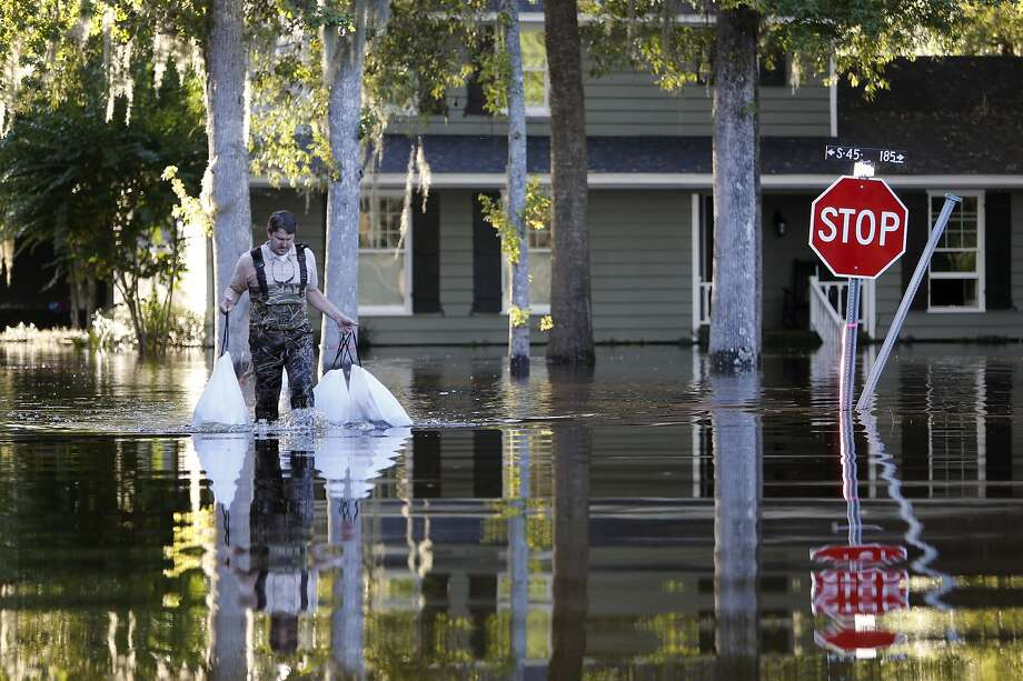"""Kevin Cox wades through floodwaters by his home in Kingstree, S.C. Gov. Nikki Haley warned residents that an expected second round of flooding may be """"a different kind of bad."""" Photo: Mic Smith, Associated Press"""