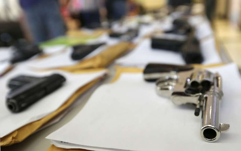 FILE - In this Monday, July 7, 2014, file photo, Chicago police display some of the thousands of illegal firearms they have confiscated so far this year in their battle against gun violence in Chicago. The recent mass shooting at an Oregon community college has put the debate over gun violence and gun control into the center of the presidential race. At least some of the Republicans who are running have pointed to Chicago as proof that gun control laws don't work. (AP Photo/M. Spencer Green) Photo: M. Spencer Green, Associated Press