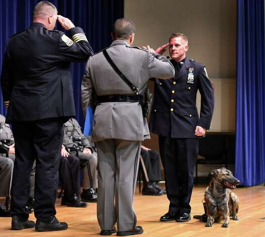 Schenectady Police officer Eric Peters, right,  salutes as he and his canine partner Liuger receive their diplomas from  Schenectady Police Chief Brian Kilcullen, left and Superintendent Joseph D'Amico, center at the New York State Police Canine Handler Basic School graduation at the State Police Academy Oct. 8, 2015 in Albany, N.Y.     (Skip Dickstein/Times Union) Photo: SKIP DICKSTEIN / 10033669A