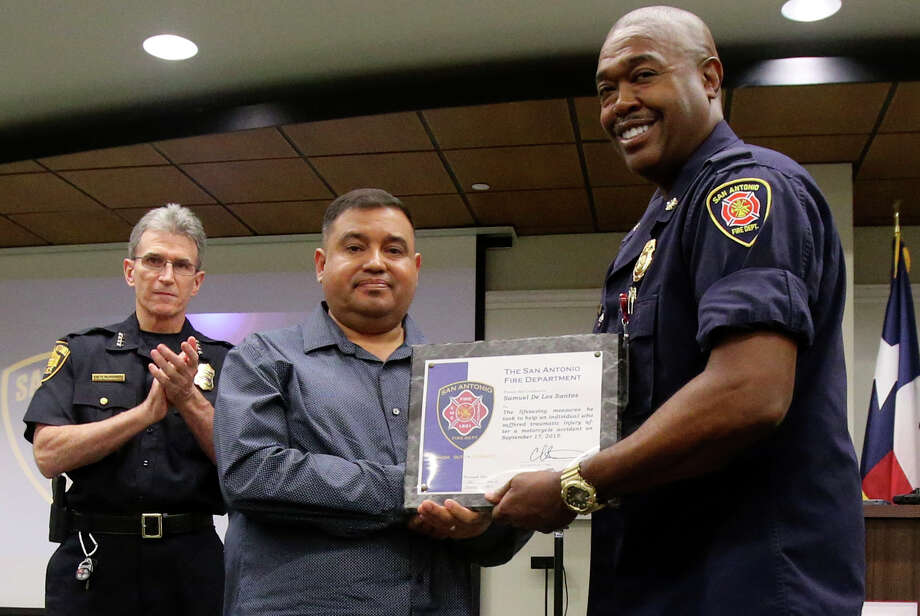 Samuel De Los Santos (center) receives recognition from San Antonio Fire Chief Charles Hood (right) Thursday October 8, 2015 at Public Safety Headquarters. De Los Santos and San Antonio police officer Oscar Torres (not pictured) and Alamo Community College Police officer Mary Ramirez (not pictured) were recognized for their life saving efforts when motorcyclist Aaron Beaugard,22, crashed his bike September 17 at Loop 1604 and Wiseman, resulting in the loss of both of his legs and other injuries. Beaugard is still recovering from his injuries. Standing on the far left in the background is San Antonio Police Chief William McManus. Photo: John Davenport, San Antonio Express-News / ©San Antonio Express-News/John Davenport