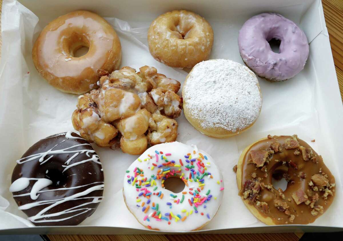 A box of donuts is shown at Lee's Fried Chicken and Donuts, 601 Heights, is shown Thursday, Oct. 8, 2015, in Houston. Shown on front row from left, Mexican chocalte icing, birthday cake icing and sprinkles, praline bacon and caramel icing, second row from left, apple fritter, and jam filled powdered sugar, back row from left, glazed, vanilla cake, and blueberry.