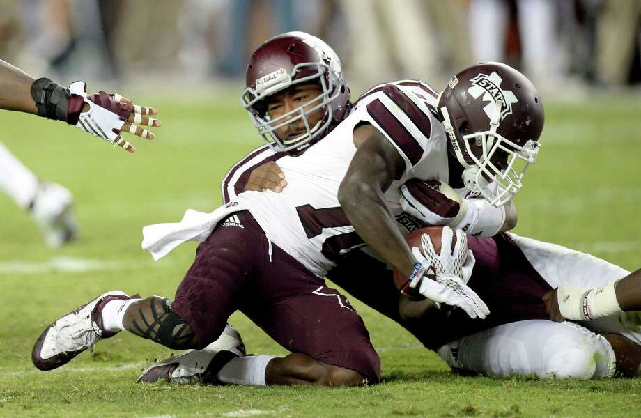 Texas A&M's Myles Garrett (15) brings down Mississippi State running back Bradnon Holloway (10) for a loss on Oct. 3, 2015, in College Station. Texas A&M won 30-17. Photo: Sam Craft /Bryan-College Station Eagle / The Bryan-College Station Eagle