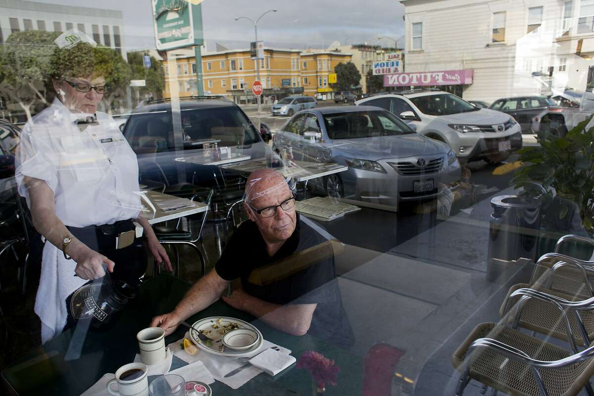Marianne Hinge-Crossan warms up Ron Jones's cup of coffee at Mel's Drive-In on Geary Boulevard. Jones, who eats at the diner nearly every day, wrote a book about his childhood growing up in the Sunset District from a booth at Mel's. (Photo by Erin Brethauer)