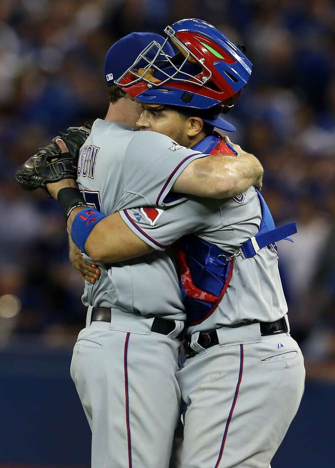 Sam Dyson (left) and Robinson Chirinos hug. Photo: Vaughn Ridley, Getty Images