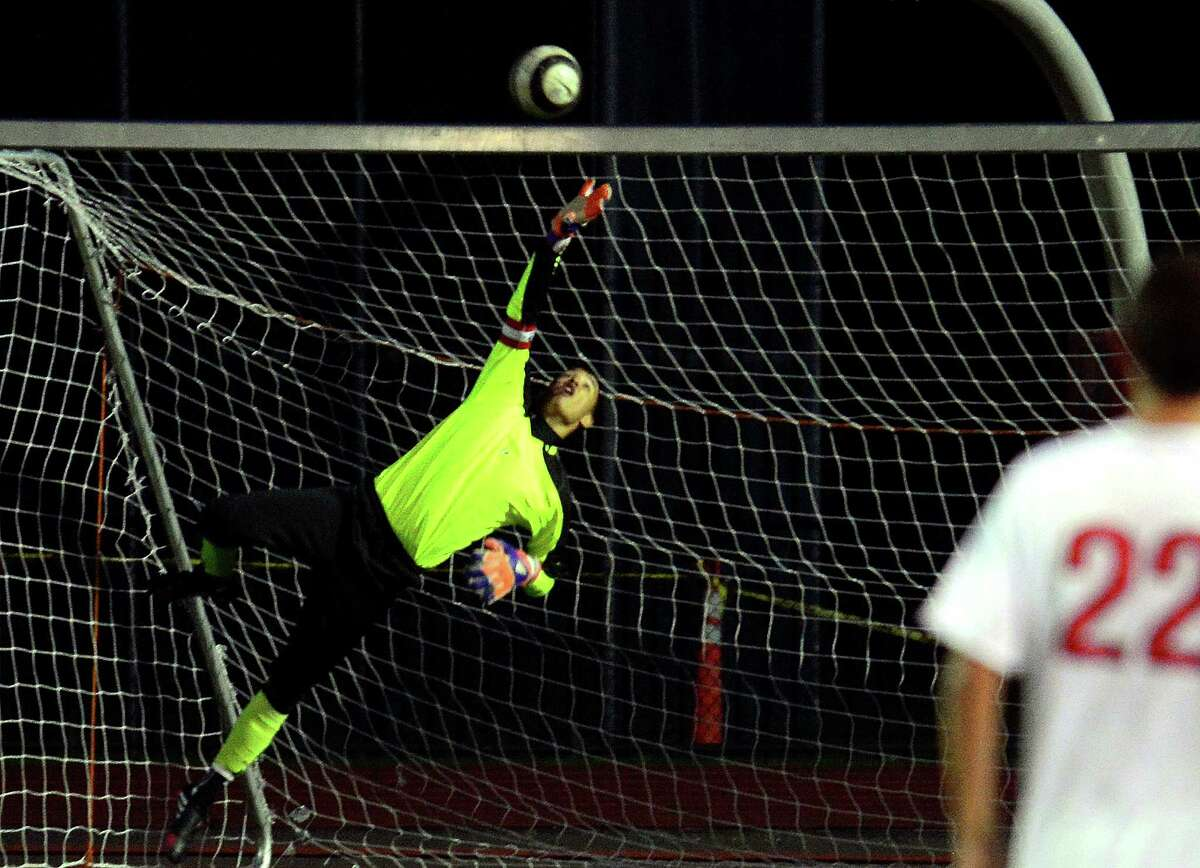Central goalie Andres Palacio reaches but is unable to stop a score by Greenwich's Nick Bartels during boys soccer action in Bridgeport, Conn. on Thursday October 8, 2015.