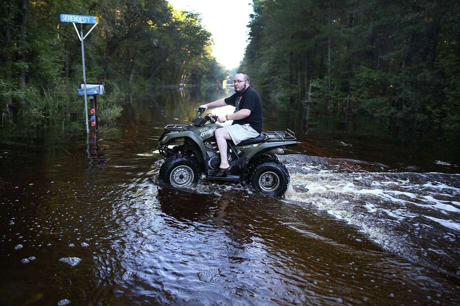 GIVHANS, SC - OCTOBER 08:  Christopher Bongiorno rides his ATV on a flooded road near his home as water that breached dams upstream reach areas in the eastern part of the state on October 8, 2015 in Givhans South Carolina.  The state of South Carolina experienced record rainfall amounts over the weekend and officials expect the damage from the flooding waters to be in the billions of dollars.  (Photo by Joe Raedle/Getty Images) Photo: Joe Raedle, Staff / Getty Images / 2015 Getty Images