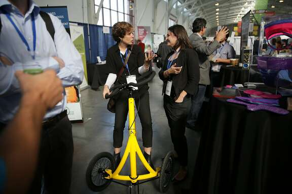 Jennifer North (l to r), Alinker Inventions chief financial officer and Diana Sierra, co-founder BeGirl.org, talk as North rides an Alinker while talking with Sierra at the BeGirl.org booth during Socap2015 at Fort Mason on Wednesday, October 7,  2015 in San Francisco, Calif.