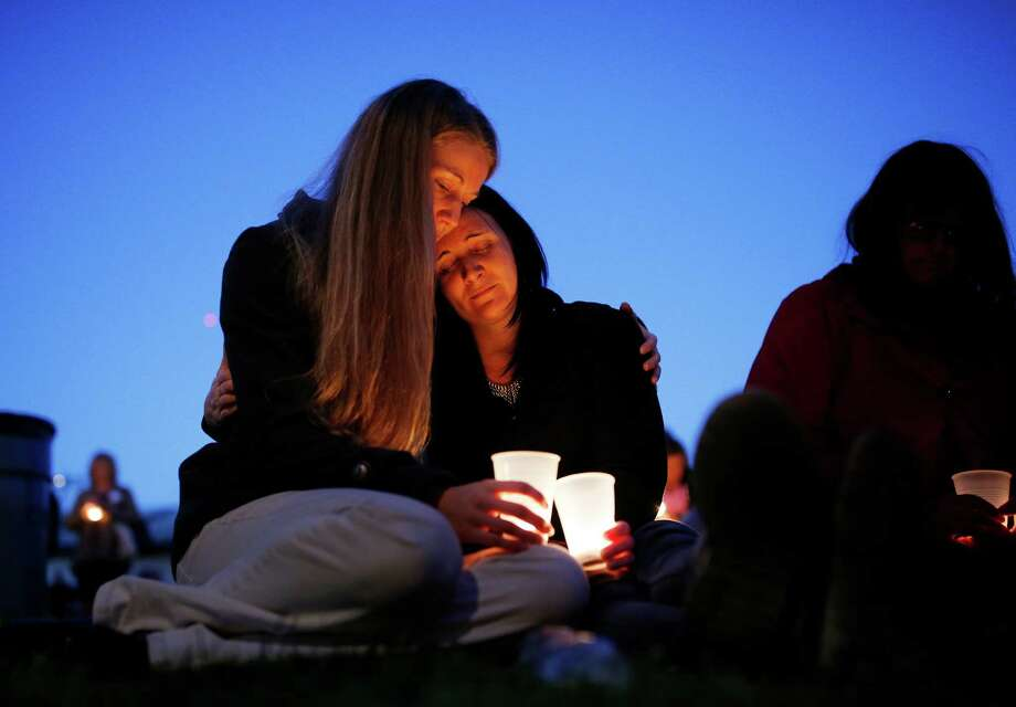 Heidi Wickersham, left, embraces her sister Gwendoline Wickersham during a prayer vigil in honor of the victims of the fatal shooting at Umpqua Community College in Roseburg, Ore. Photo: John Locher, STF / AP