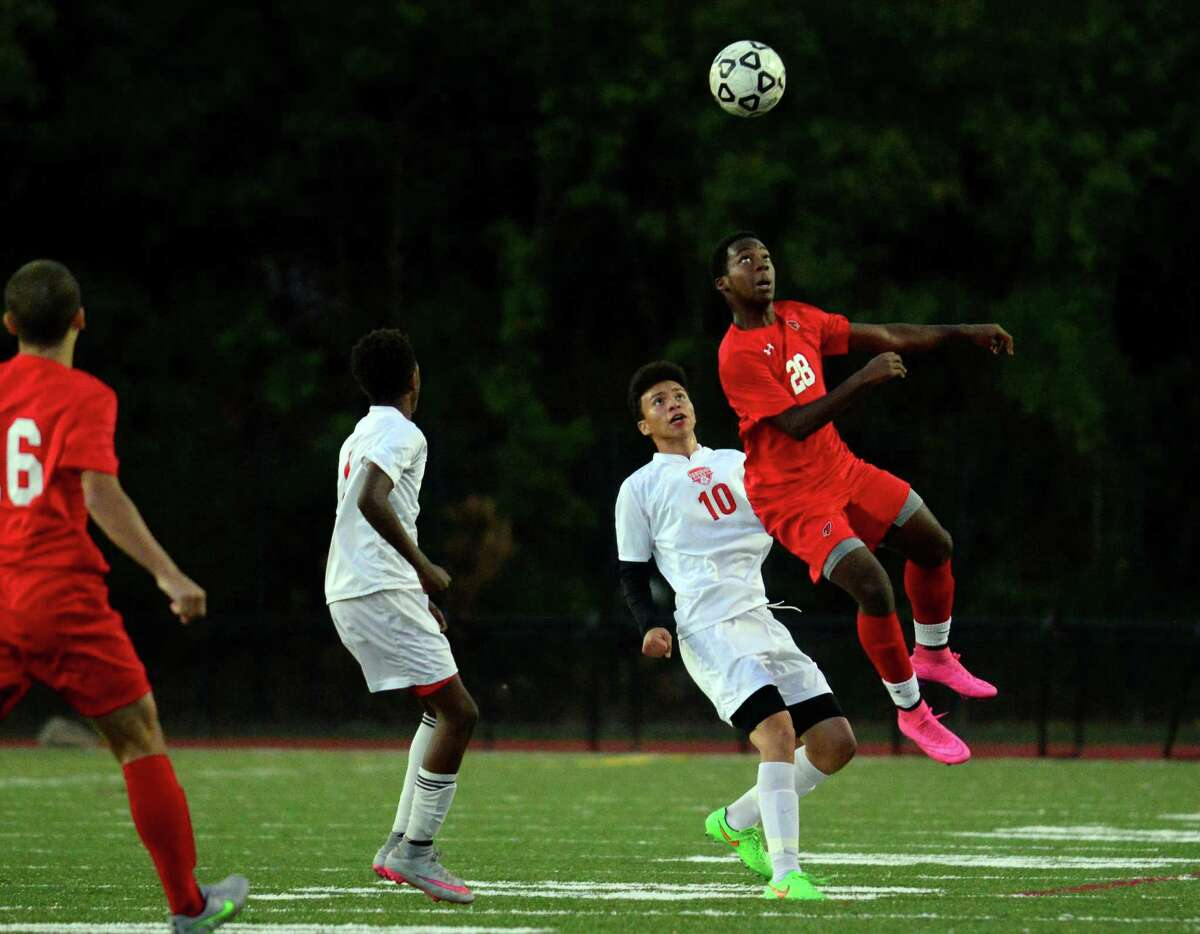 Greenwich's Flavien Lolo prepares to head the ball during boys soccer action against Central in Bridgeport, Conn. on Thursday October 8, 2015.