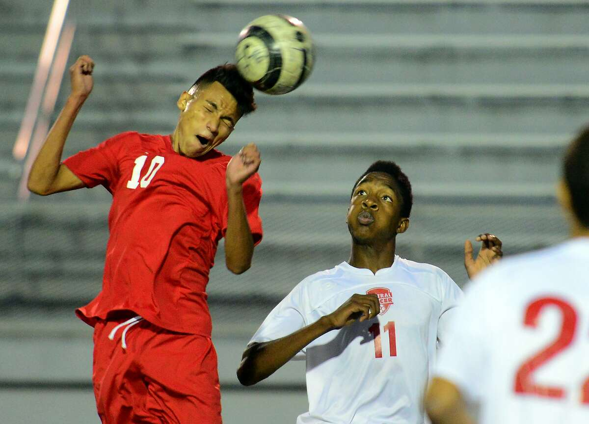 Greenwich's Nico Ortiz heads the ball during boys soccer action against Central in Bridgeport, Conn. on Thursday October 8, 2015. In center is Central's Akeem Mitchell.