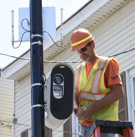 Jeff Smith of the Stilsing Company puts the finishing touches on a red-light camera that looks in to the intersection of Quail Street and Washington Avenue Thursday afternoon July 16, 2015 in Albany, N.Y. (Skip Dickstein/Times Union)